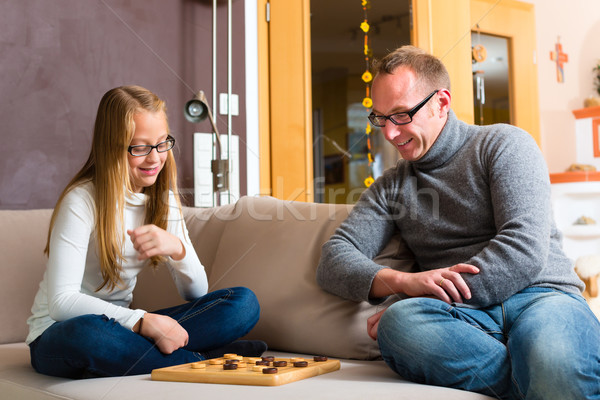 Father and daughter playing checkers Stock photo © Kzenon