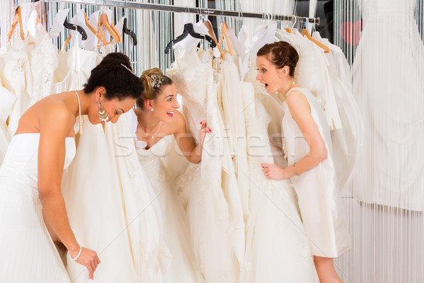 Women having fun during bridal dress fitting in shop Stock photo © Kzenon