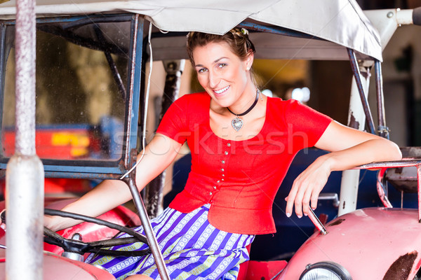 Bavarian woman with Dirndl dress driving tractor Stock photo © Kzenon