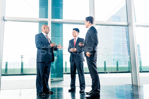 Három üzletemberek áll iroda lobbi városkép Stock fotó © Kzenon