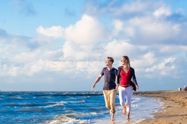 Couple running through sand and waves at beach Stock photo © Kzenon
