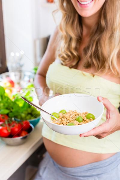 Donna incinta mangiare sano muesli frutta piedi contatore di cucina Foto d'archivio © Kzenon