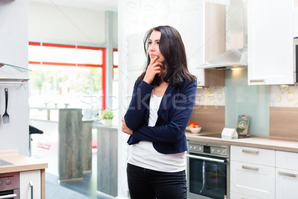 Woman buying domestic kitchen in furniture store Stock photo © Kzenon
