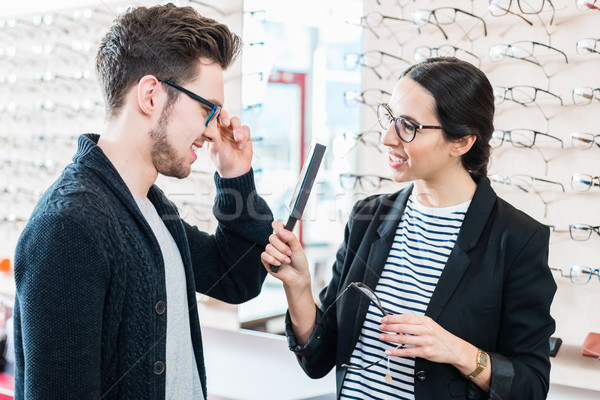 Woman and man buying glasses in optician shop Stock photo © Kzenon