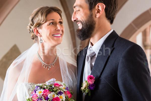 Bride and groom marrying at church wedding Stock photo © Kzenon