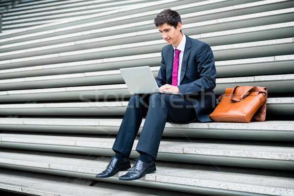 Young businessman using a laptop while sitting down outdoors  Stock photo © Kzenon