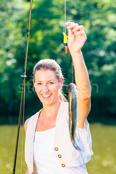 Sport fisherwoman showing her catch  Stock photo © Kzenon