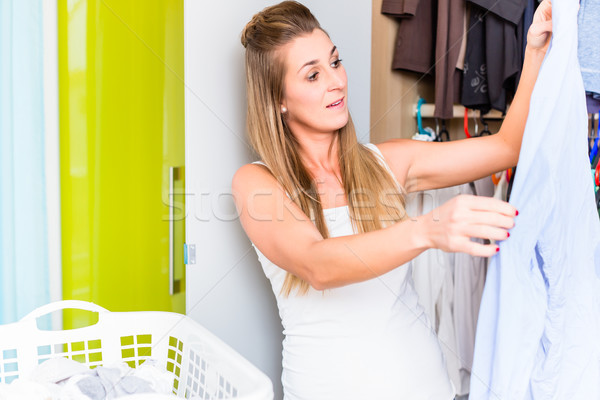 Woman in front of wardrobe in bedroom folding laundry Stock photo © Kzenon