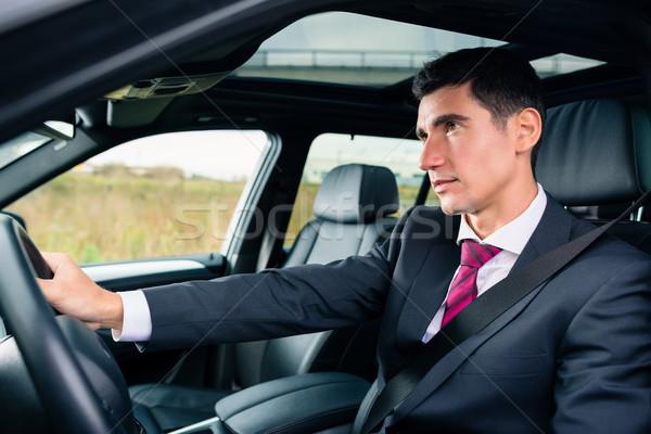 Man driving in his car in business attire Stock photo © Kzenon