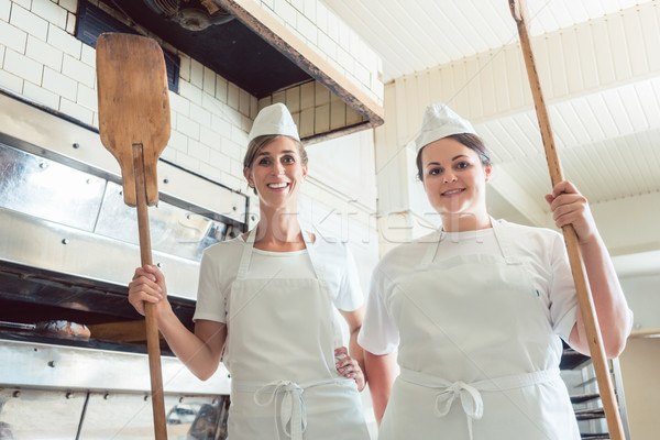 Team of baker women standing in bakery giving thumbs up Stock photo © Kzenon
