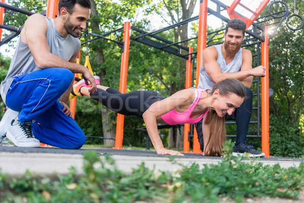 Stock photo: Fit woman doing leg extension with suspension trainer motivated