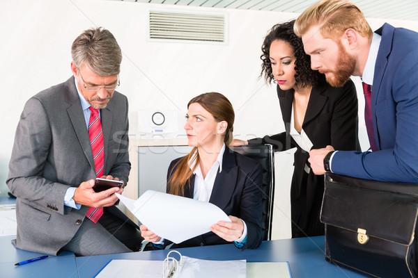 Team discussing status of a contract Stock photo © Kzenon