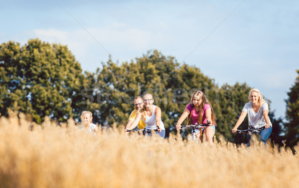 Stock photo: Family riding their bikes shot above a grain field