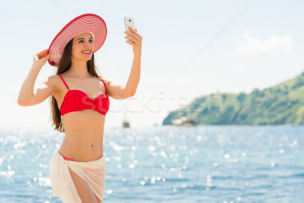 Beautiful young woman wearing a trendy striped hat at the beach Stock photo © Kzenon