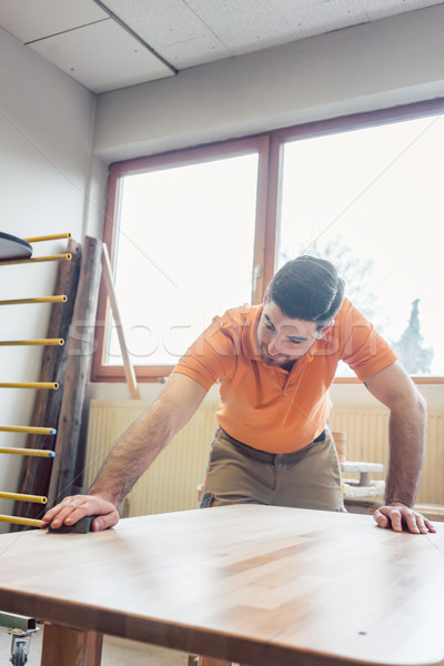 Carpenter polishing and varnishing a table Stock photo © Kzenon