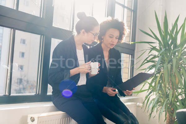 Two young colleagues reviewing business reports during break Stock photo © Kzenon