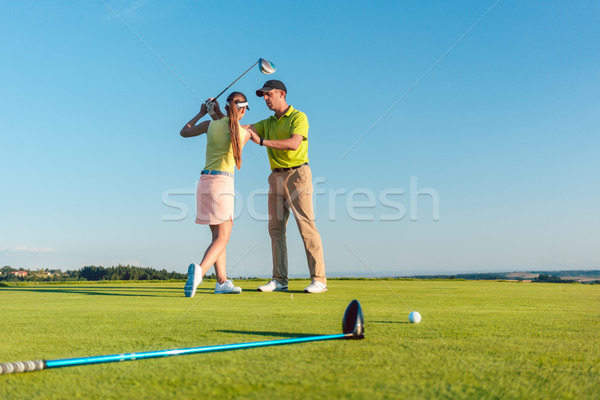 Golf instructor teaching a young woman to swing the driver club  Stock photo © Kzenon