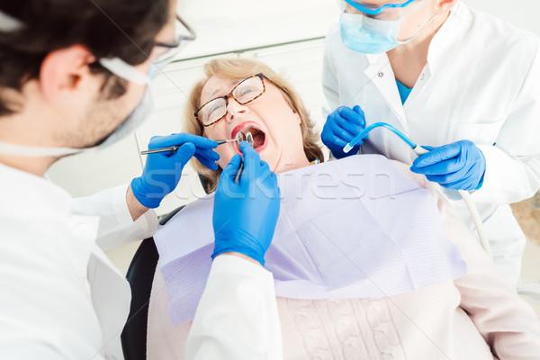 Dentist during treatment of a senior patient Stock photo © Kzenon