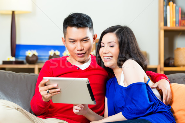 Asian couple on the couch with a tablet pc Stock photo © Kzenon