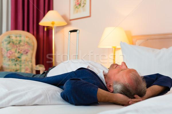 Senior man lying on the bed in the hotel room Stock photo © Kzenon