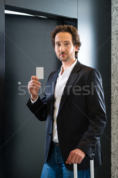 Businessman with key card for room door in hotel Stock photo © Kzenon