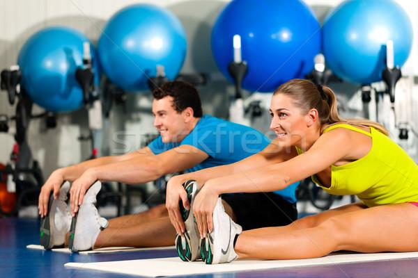 Couple in gym stretching Stock photo © Kzenon
