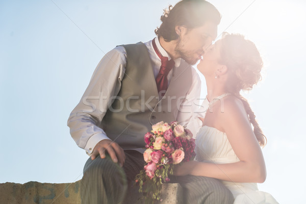 Bridal pair kissing on field after wedding Stock photo © Kzenon