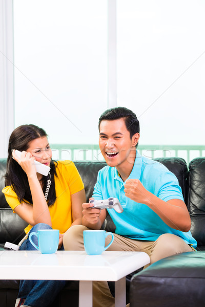 Asian couple playing video games and phone Stock photo © Kzenon