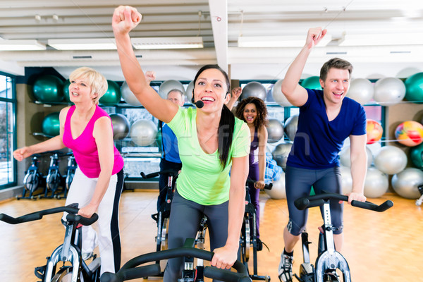 Stock photo: Group of men and women spinning on fitness bikes in gym