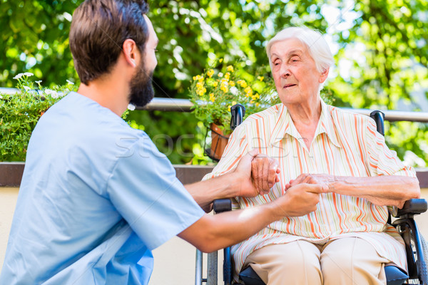 Geriatric nurse holding hand of old woman in rest home Stock photo © Kzenon