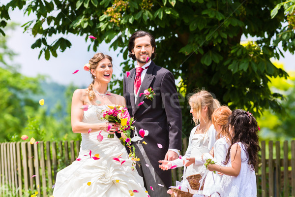 Wedding couple and bridesmaid showering flowers Stock photo © Kzenon