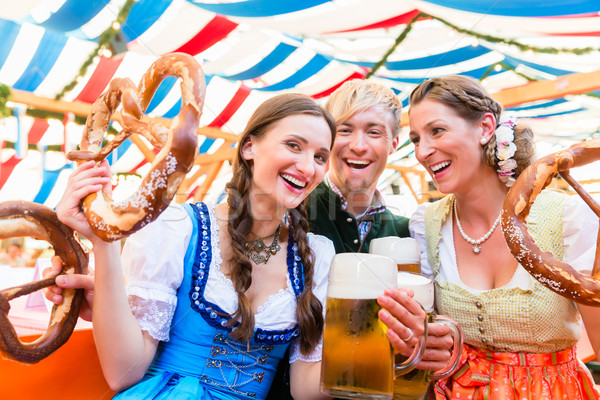 Friends with giant pretzels in Bavarian beer tent Stock photo © Kzenon