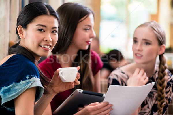 Young woman showing paperwork to her friends Stock photo © Kzenon