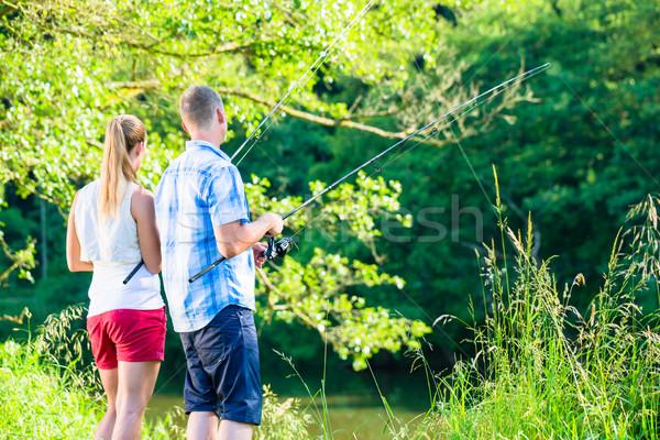 Balık tutma adam kadın birlikte çubuk nehir Stok fotoğraf © Kzenon