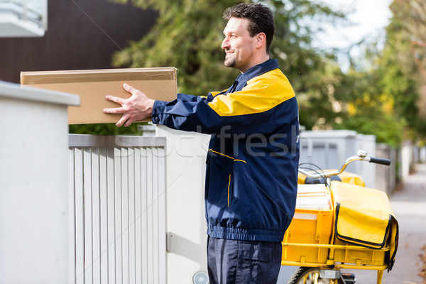 Postman delivering packet wrapped as present Stock photo © Kzenon