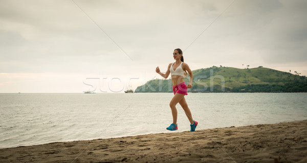 Fit young woman running on the beach during summer vacation in F Stock photo © Kzenon