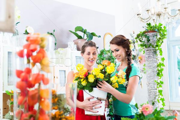 Stock photo: Women in flower store enjoying the roses