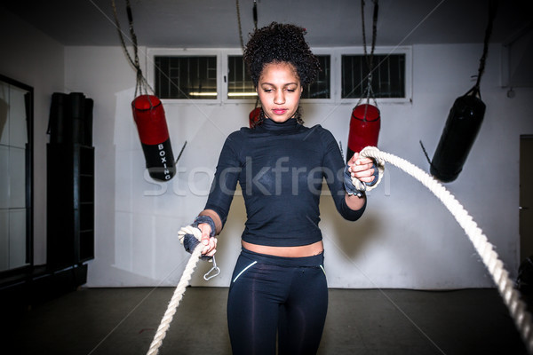 Young fit woman exercising with battle ropes during functional training Stock photo © Kzenon