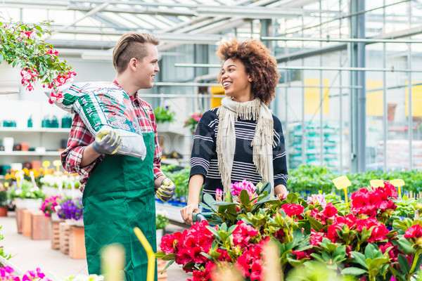 Cheerful handsome worker in a flower shop talking with a beautiful customer Stock photo © Kzenon