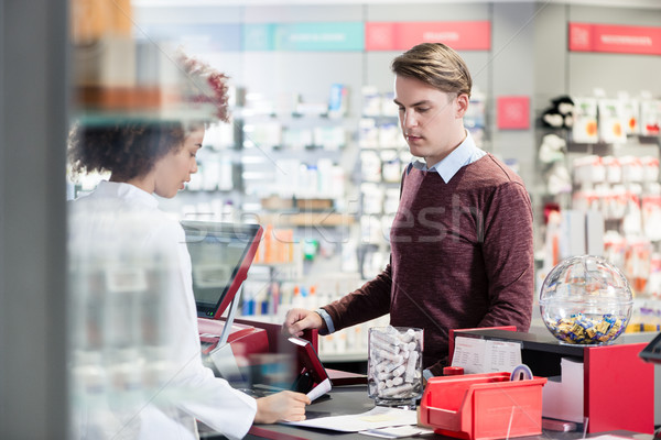 Young man smiling while buying an useful pharmaceutical product  Stock photo © Kzenon