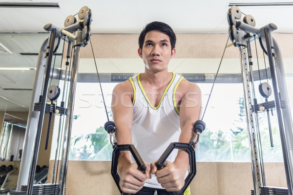 Asian handsome man exercising cable crossover for chest muscles  Stock photo © Kzenon
