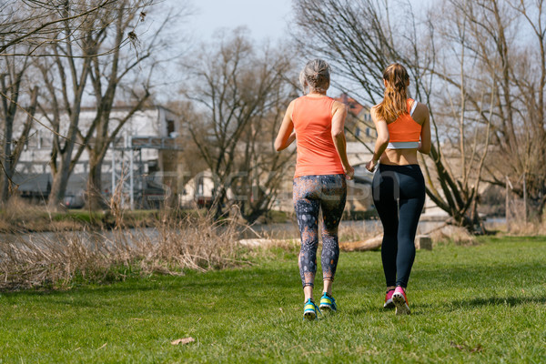 Mother and adult daughter running for sport along the river Stock photo © Kzenon