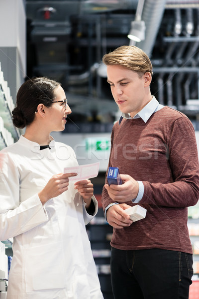 young man holding two medicines while looking at various products Stock photo © Kzenon