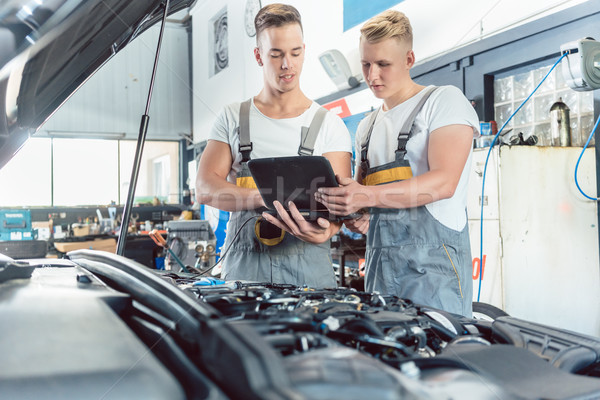 Experienced auto mechanic using a laptop for scanning engine errors Stock photo © Kzenon
