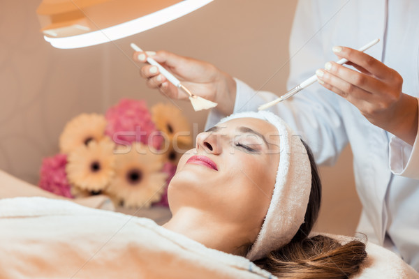 Beautiful woman during anti-aging facial massage in a modern cosmetic center Stock photo © Kzenon