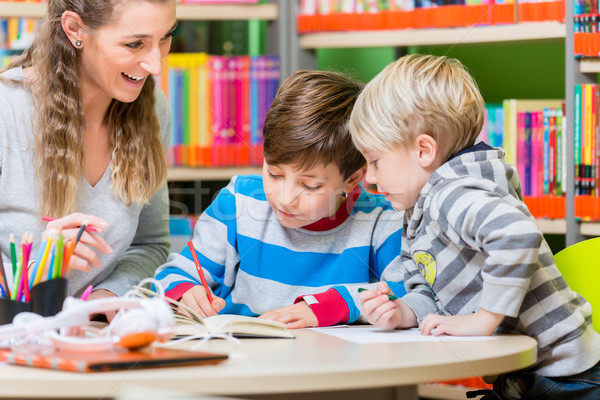 Mom with her two sons spending time in the library Stock photo © Kzenon