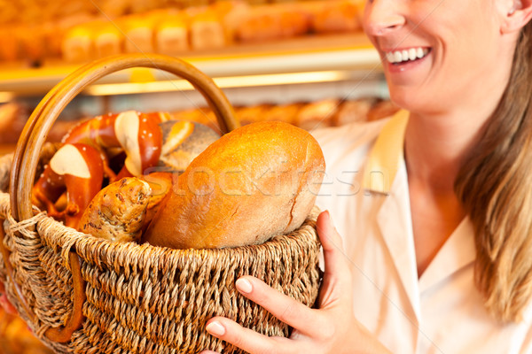 Female baker selling bread by basket in bakery Stock photo © Kzenon