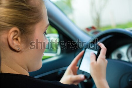 Young woman, in car with mobile phone  Stock photo © Kzenon