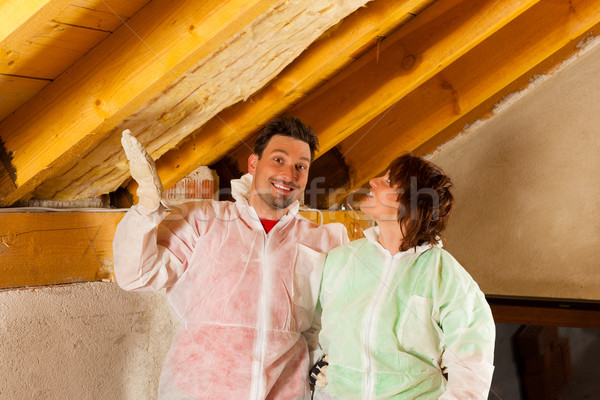 Couple installing thermal insulation to roof Stock photo © Kzenon