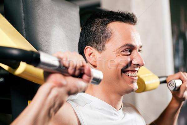 Man exercising and training in gym Stock photo © Kzenon